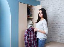 Το κορίτσι εφήβων παίρνει το πουκάμισο από την ντουλάπα Στοκ Εικόνα