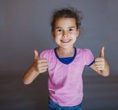 Το κορίτσι εφήβων παρουσιάζει χειρονομία ναι στο γκρίζο υπόβαθρο Στοκ Φωτογραφίες