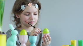 Το κορίτσι εφήβων προετοιμάζει τις διακοσμήσεις για τις διακοπές Πάσχας Αυγά Πάσχας χρωμάτων με μια βούρτσα, χαμόγελα που στενοχω φιλμ μικρού μήκους