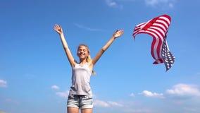 Το κορίτσι εφήβων ρίχνει την ΑΜΕΡΙΚΑΝΙΚΗ σημαία στον αέρα απόθεμα βίντεο