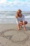 Το κορίτσι εφήβων σε ένα άσπρο φόρεμα επισύρει την προσοχή την καρδιά στην άμμο Στοκ Φωτογραφία