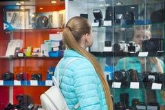 Το κορίτσι εφήβων στο κατάστημα phototechnique επιλέγει τη ψηφιακή κάμερα στοκ φωτογραφία με δικαίωμα ελεύθερης χρήσης