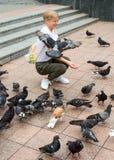 Το κορίτσι εφήβων ταΐζει τα περιστέρια Στοκ Εικόνα