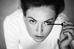 Το κορίτσι εφαρμόζει mascara Αρκετά χαριτωμένο κορίτσι με mascara Στοκ Εικόνες