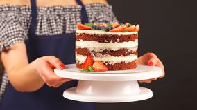 Το κορίτσι ζαχαροπλαστών κρατά δύο χέρια ένα εύγευστο κέικ φιλμ μικρού μήκους