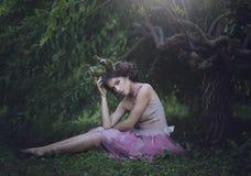 Το κορίτσι η πριγκήπισσα με τα κέρατα καθμένος κάτω από ένα δέντρο Μυστικό πλάσμα κοριτσιών fawn στα shabby ενδύματα σε ένα δάσος στοκ φωτογραφία με δικαίωμα ελεύθερης χρήσης