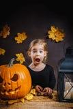 Το κορίτσι θέτει με μια κολοκύθα αποκριών Στοκ Φωτογραφία
