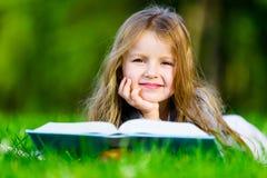 Το κορίτσι διαβάζει το ενδιαφέρον βιβλίο στη χλόη στοκ εικόνες