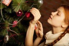 Το κορίτσι διακοσμεί το χριστουγεννιάτικο δέντρο Στοκ εικόνα με δικαίωμα ελεύθερης χρήσης