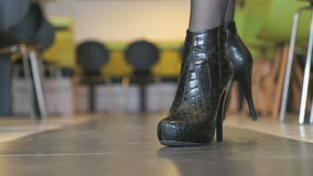 Το κορίτσι διαφημίζει τις κοντές μπότες από το δέρμα κροκοδείλων φιλμ μικρού μήκους