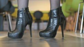 Το κορίτσι διαφημίζει τις κοντές μπότες από το δέρμα κροκοδείλων απόθεμα βίντεο