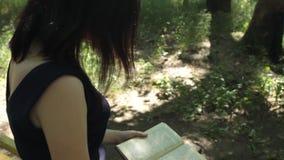Το κορίτσι κάθεται και διαβάζει ένα βιβλίο στο πάρκο απόθεμα βίντεο