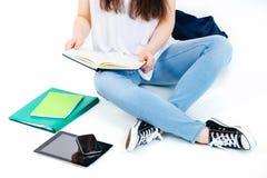Το κορίτσι κάθεται και εξετάζει το βιβλίο Στοκ Φωτογραφία