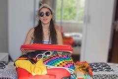 Το κορίτσι κάθεται κοντά στη βαλίτσα Κορίτσι εκτός από την υπερχειλισμένη βαλίτσα Να πάρει έτοιμος για το ταξίδι Καλημέρα για ένα Στοκ Φωτογραφίες