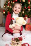 Το κορίτσι κάθεται κοντά στο δέντρο και το παιχνίδι έλατου Χριστουγέννων με την αρκούδα, διακόσμηση Χριστουγέννων στο σπίτι, ευτυ στοκ εικόνες