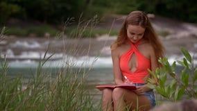 Το κορίτσι κάθεται με το σημειωματάριο εγγράφου ενάντια στο Foamy ποταμό απόθεμα βίντεο