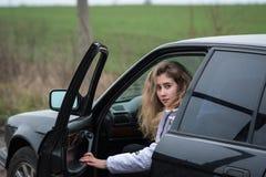 Το κορίτσι κάθεται πίσω από τη ρόδα στο αυτοκίνητο και τις στροφές γύρω Στοκ φωτογραφίες με δικαίωμα ελεύθερης χρήσης