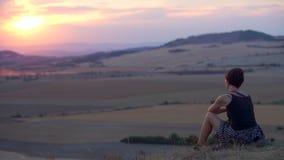 Το κορίτσι κάθεται πίσω σε έναν λόφο και εξετάζει την απόσταση του βουνού απόθεμα βίντεο