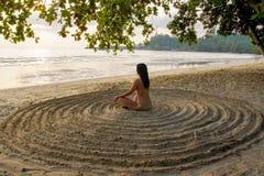 Το κορίτσι κάθεται πίσω στην αμμώδη παραλία στο κέντρο ενός αυτοσχέδιου κύκλου και meditates στοκ εικόνα με δικαίωμα ελεύθερης χρήσης
