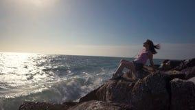 Το κορίτσι κάθεται σε έναν βράχο και εξέταση τα κύματα φιλμ μικρού μήκους