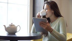 Το κορίτσι κάθεται σε έναν πίνακα και ένα τσάι κατανάλωσης με ένα PC ταμπλετών στα χέρια απόθεμα βίντεο