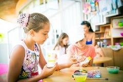 Το κορίτσι κάθεται σε έναν πίνακα και διακοσμεί το ειδώλιο αργίλου Στοκ Εικόνες