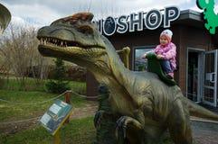Το κορίτσι κάθεται σε Dilophosaurus στο πάρκο δεινοσαύρων, Μόσχα, Ρωσία στοκ εικόνες