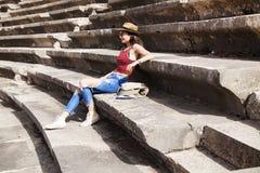 Το κορίτσι κάθεται στα βήματα του ταξιδιού αμφιθεάτρων στην Τουρκία, τα μνημεία της αρχαίας αρχιτεκτονικής στοκ φωτογραφίες με δικαίωμα ελεύθερης χρήσης