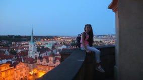 Το κορίτσι κάθεται το στηθαίο στο υπόβαθρο της πόλης νύχτας φιλμ μικρού μήκους