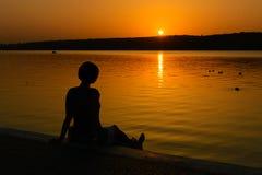 Το κορίτσι κάθεται στην ακτή μιας λίμνης στην πόλη και εξετάζει το ηλιοβασίλεμα Στοκ εικόνα με δικαίωμα ελεύθερης χρήσης