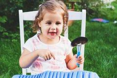 Το κορίτσι κάθεται στην καρέκλα στον κήπο με μια μεγάλη συλλογή των βουρτσών για αποτελεί Στοκ εικόνες με δικαίωμα ελεύθερης χρήσης