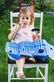 Το κορίτσι κάθεται στην καρέκλα στον κήπο με μια μεγάλη συλλογή των βουρτσών για αποτελεί Στοκ φωτογραφία με δικαίωμα ελεύθερης χρήσης