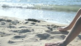 Το κορίτσι κάθεται στην παραλία και χύνει έξω την άμμο από τους φοίνικές της φιλμ μικρού μήκους
