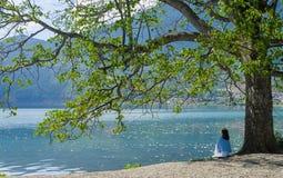 Το κορίτσι κάθεται στην παραλία ανατρέχοντας, πίσω στη κάμερα Στοκ φωτογραφίες με δικαίωμα ελεύθερης χρήσης