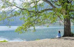 Το κορίτσι κάθεται στην παραλία ανατρέχοντας, πίσω στη κάμερα Στοκ Εικόνες