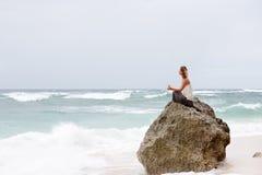 Το κορίτσι κάθεται στην παραλία στο βράχο και meditating στη γιόγκα θέστε Στοκ Εικόνες