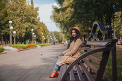 Το κορίτσι κάθεται στον πάγκο στο παλτό και τα κόκκινα παπούτσια Στοκ εικόνες με δικαίωμα ελεύθερης χρήσης