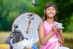 Το κορίτσι κάθεται στον πίνακα και την εκμετάλλευση ένα φλυτζάνι του τσαγιού Alice Στοκ Εικόνα