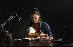 Το κορίτσι κάθεται στον πίνακα και τη μελέτη στοκ φωτογραφίες