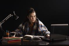 Το κορίτσι κάθεται στον πίνακα και τη μελέτη στοκ εικόνα με δικαίωμα ελεύθερης χρήσης