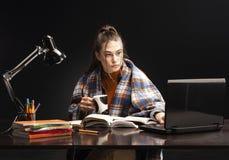 Το κορίτσι κάθεται στον πίνακα και τη μελέτη στοκ εικόνα