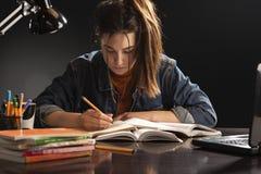 Το κορίτσι κάθεται στον πίνακα και τη μελέτη στοκ φωτογραφίες με δικαίωμα ελεύθερης χρήσης