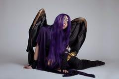 Το κορίτσι κάθεται στον πορφυρό χαρακτήρα κοστουμιών μανίας cosplay Στοκ Εικόνες