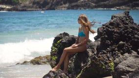 Το κορίτσι κάθεται στο βράχο και εξετάζει τη θάλασσα Μπαλί Ινδονησία Στοκ φωτογραφίες με δικαίωμα ελεύθερης χρήσης