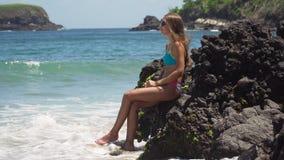 Το κορίτσι κάθεται στο βράχο και εξετάζει τη θάλασσα Μπαλί Ινδονησία απόθεμα βίντεο