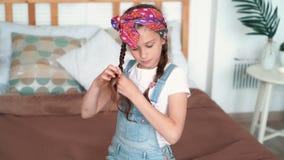 Το κορίτσι κάθεται στο κρεβάτι, πλέκει την τρίχα της στις πλεξούδες και εξετάζει τη κάμερα, σε αργή κίνηση φιλμ μικρού μήκους