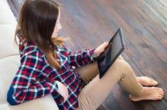 Το κορίτσι κάθεται στο πάτωμα με μια ταμπλέτα στα χέρια της διαβάζοντας τις ειδήσεις στοκ φωτογραφίες με δικαίωμα ελεύθερης χρήσης