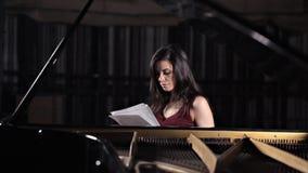 Το κορίτσι κάθεται στο πιάνο και μαθαίνει τη μουσική, σημειώνει Μουσικ απόθεμα βίντεο