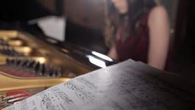Το κορίτσι κάθεται στο πιάνο και μαθαίνει τη μουσική, σημειώνει Μουσικ φιλμ μικρού μήκους
