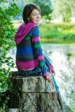 Το κορίτσι κάθεται στο στέλεχος Στοκ Εικόνες